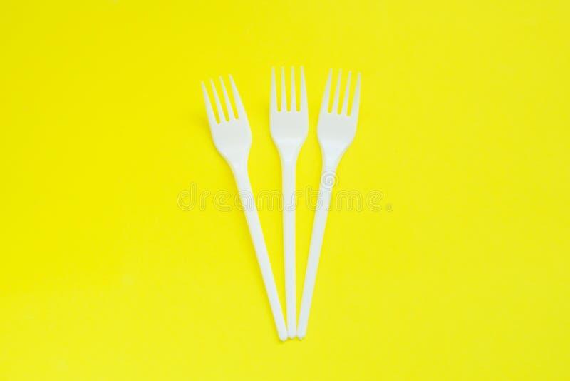 Μίας χρήσης πλαστικά βουλώματα στο φωτεινό κίτρινο υπόβαθρο με το διάστημα αντιγράφων στοκ εικόνα