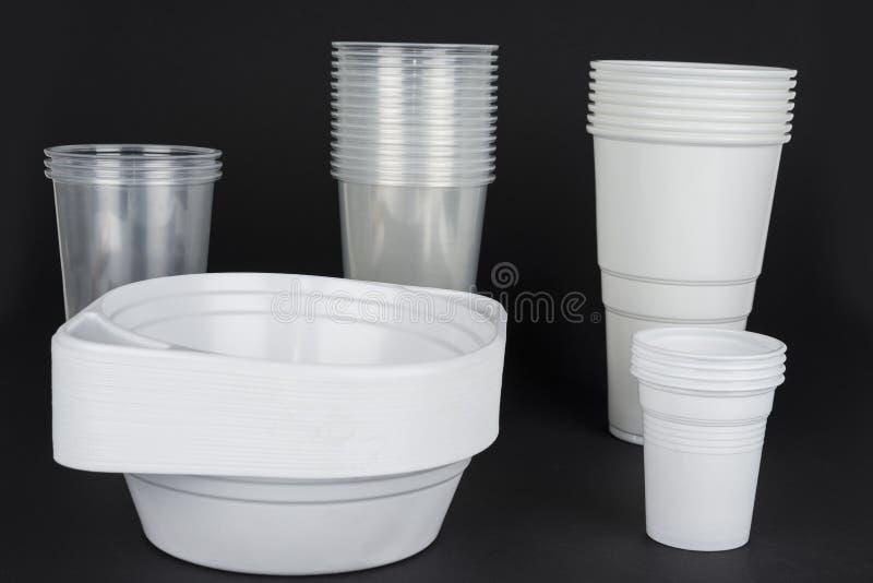 Μίας χρήσης πλαστικά εμπορεύματα σε ένα μαύρο υπόβαθρο στοκ εικόνες
