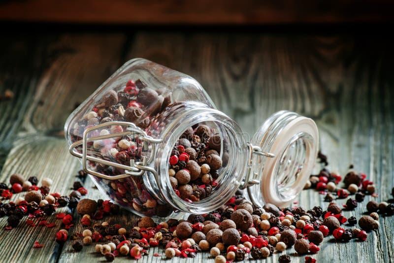 Μίγμα από πέντε πιπέρια σε ένα βάζο γυαλιού στον παλαιό ξύλινο πίνακα, επίλεκτο στοκ φωτογραφίες με δικαίωμα ελεύθερης χρήσης
