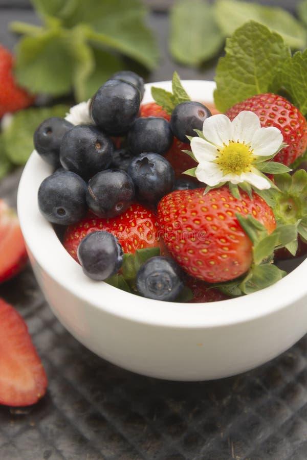 Μίγμα μούρων σε ένα κύπελλο Φρέσκα θερινά φράουλες και βακκίνια με τα φύλλα μεντών Φρούτα για το καταφερτζή r στοκ φωτογραφίες με δικαίωμα ελεύθερης χρήσης