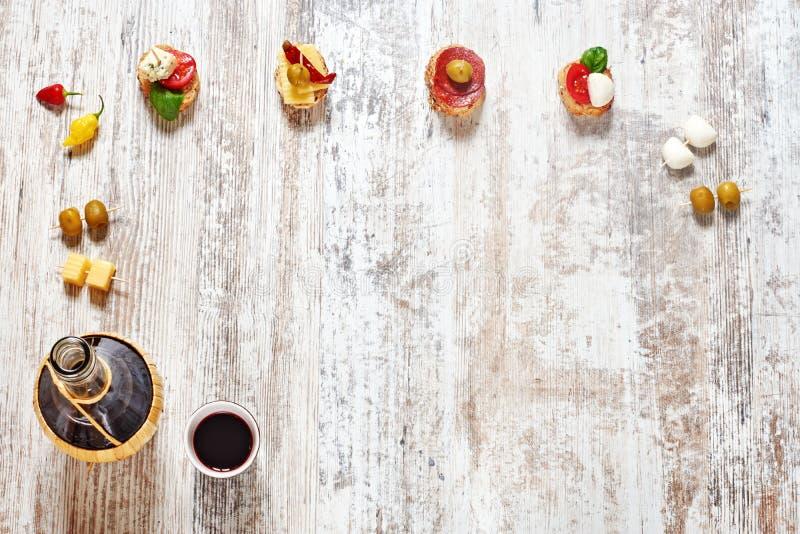 Μίγμα των ορεκτικών/των πρόχειρων φαγητών και ενός μπουκαλιού του κόκκινου κρασιού στοκ εικόνα