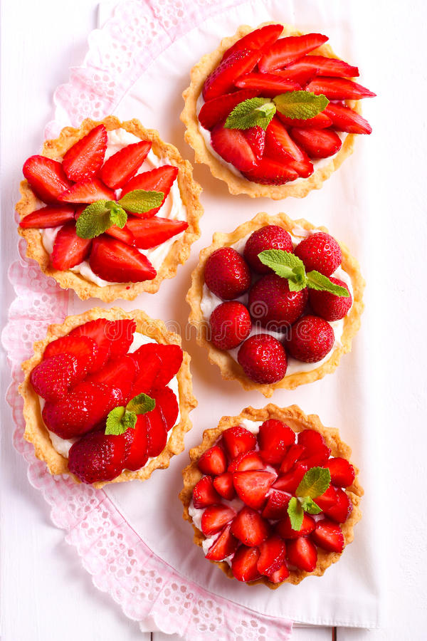 Μίνι κέικ τυριών φραουλών και κρέμας στον πίνακα στοκ φωτογραφίες