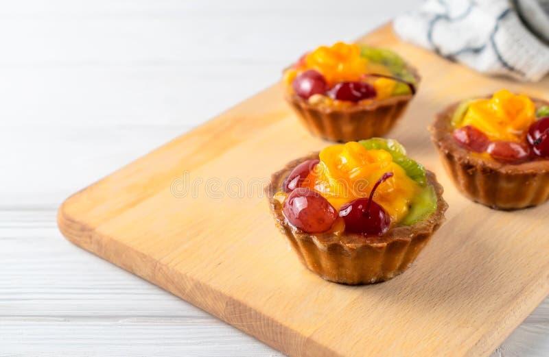 Μίνι μικτά tarts φρούτων με το πορτοκαλιά κεράσι και το ακτινίδιο στο ξύλινο πιάτο στοκ εικόνα