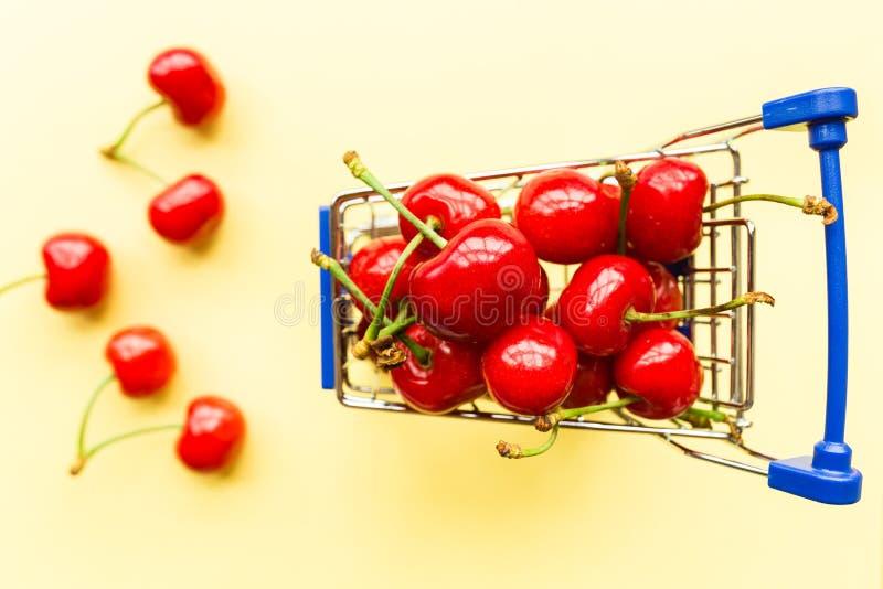 Μίνι σύνολο κάρρων παντοπωλείων αγορών των φρέσκων κερασιών Φρέσκα μούρα στο κίτρινο υπόβαθρο Έννοια υγιών, θερινών τροφίμων r στοκ φωτογραφία με δικαίωμα ελεύθερης χρήσης