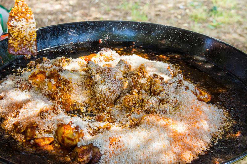Μίξη του άψητου ρυζιού με τα καρυκεύματα σάλτσας ντοματών και του τσιγαρισμένου κρέατος κουνελιών και κοτόπουλου στο μεγάλο επίπε στοκ εικόνες