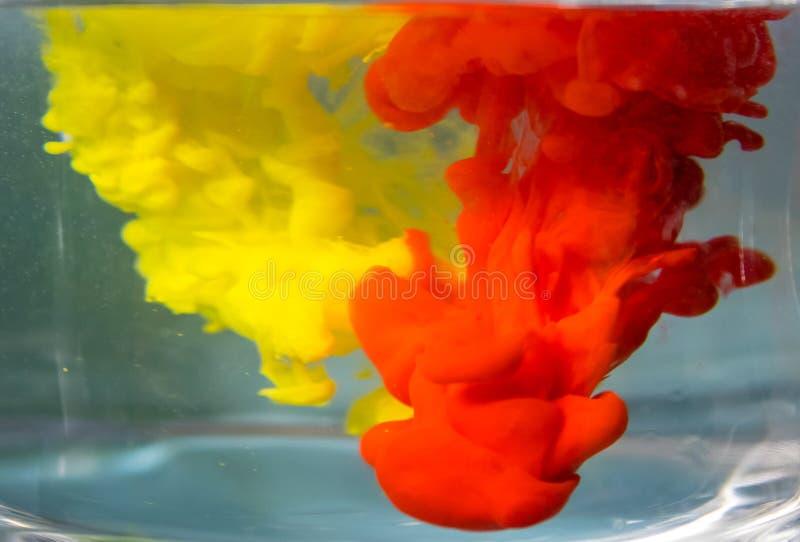 Μίξη του κίτρινου και κόκκινου χρώματος στο νερό στοκ εικόνα με δικαίωμα ελεύθερης χρήσης