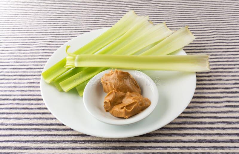 Μίσχοι σέλινου με το φυστικοβούτυρο σε ένα άσπρο πιάτο στοκ εικόνες