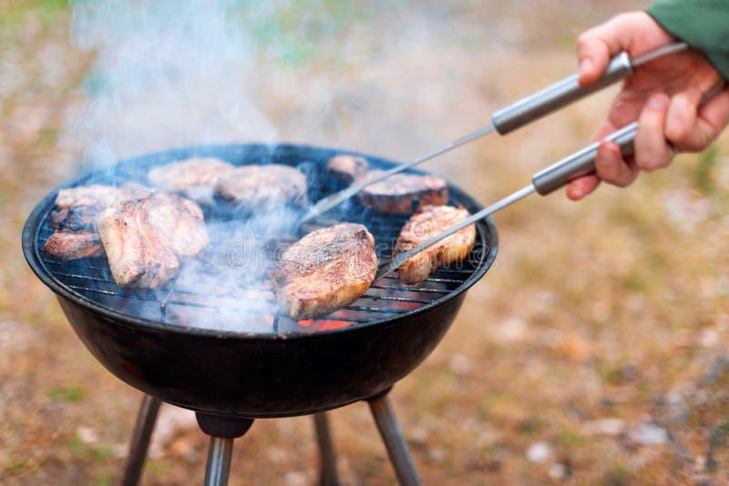 Μαγείρεμα ατόμων, μόνο χέρια, ψήνει το κρέας ή την μπριζόλα για ένα πιάτο στη σχάρα Εύγευστο ψημένο στη σχάρα κρέας στη σχάρα Σαβ στοκ εικόνες με δικαίωμα ελεύθερης χρήσης