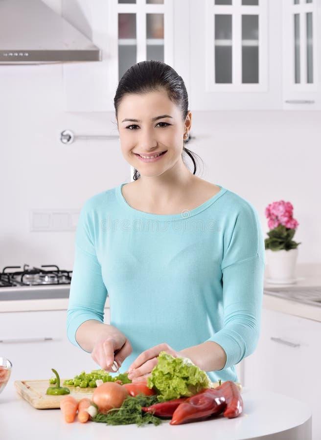 Μαγείρεμα γυναικών στη νέα κουζίνα που κατασκευάζει τα υγιή τρόφιμα με τα λαχανικά στοκ εικόνες
