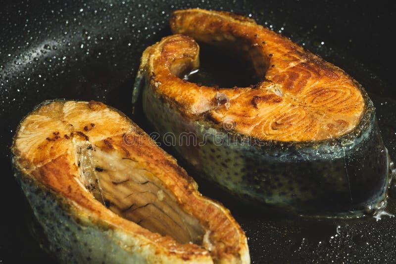 Μαγείρεμα δύο τηγανισμένων μπριζολών σολομών στο μαύρο τηγάνι στοκ εικόνες