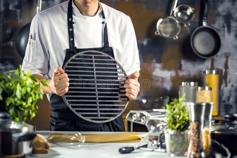 Μαγείρεμα, επάγγελμα και έννοια ανθρώπων - αρσενικός μάγειρας αρχιμαγείρων που κατασκευάζει τα τρόφιμα στην κουζίνα εστιατορίων στοκ φωτογραφία με δικαίωμα ελεύθερης χρήσης