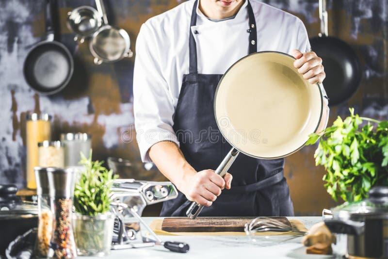 Μαγείρεμα, επάγγελμα και έννοια ανθρώπων - αρσενικός μάγειρας αρχιμαγείρων που κατασκευάζει τα τρόφιμα στην κουζίνα εστιατορίων στοκ φωτογραφίες