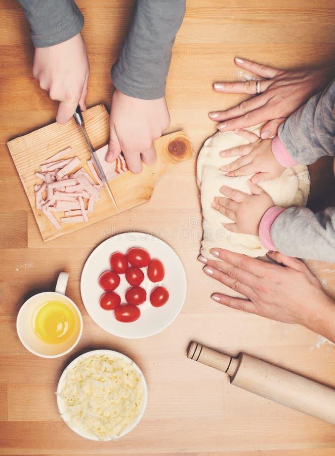 Μαγείρεμα με τα παιδιά Τα χέρια παιδιών και μητέρων ζυμώνουν και κυλούν το dou στοκ φωτογραφία
