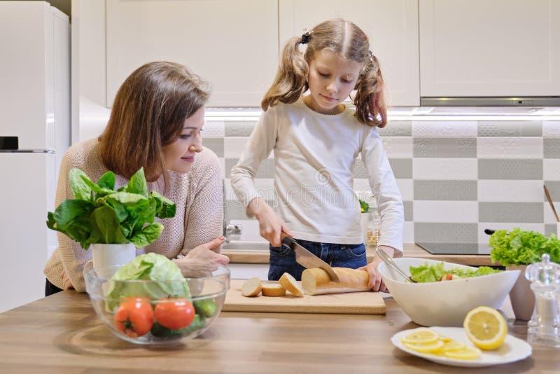 Μαγείρεμα μητέρων και κορών μαζί στην κουζίνα στο σπίτι, τέμνον ψωμί κοριτσιών στοκ φωτογραφία με δικαίωμα ελεύθερης χρήσης