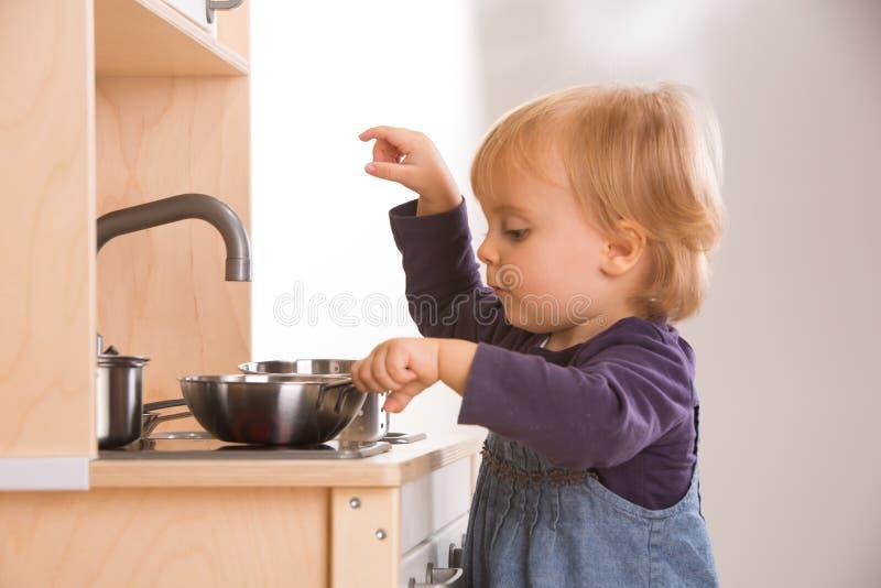 Μαγείρεμα παιχνιδιού κορών οικογενειακών κοριτσιών μωρών στην κουζίνα παιχνιδιών στοκ εικόνα με δικαίωμα ελεύθερης χρήσης