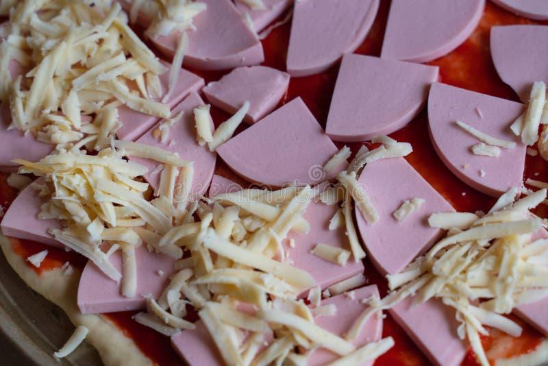 μαγείρεμα της εύγευστης πίτσας με τις φέτες της κινηματογράφησης σε πρώτο πλάνο λουκάνικων και τυριών στοκ εικόνες με δικαίωμα ελεύθερης χρήσης