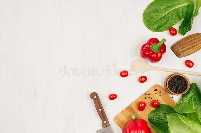 Μαγείρεμα της φρέσκιας σαλάτας άνοιξη των πράσινων και κόκκινων λαχανικών, καρυκεύματα στο άσπρο ξύλινο υπόβαθρο, σύνορα, τοπ άπο στοκ εικόνες