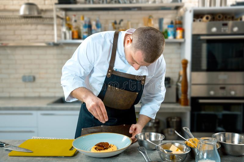 Μαγείρεμα τροφίμων, επάγγελμα και έννοια ανθρώπων - αρσενικό εξυπηρετώντας πιάτο μαγείρων αρχιμαγείρων των γλωσσών polenta και μο στοκ εικόνα
