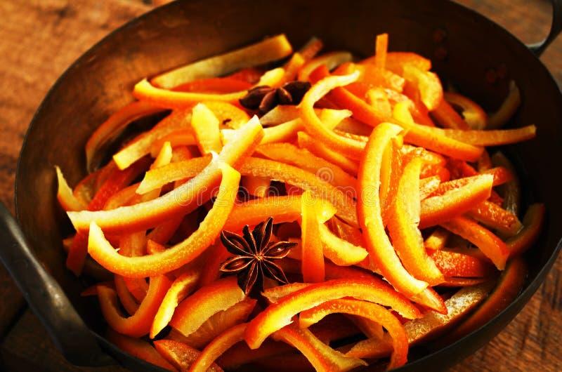 Μαγείρεμα των γλασαρισμένων πορτοκαλιών φλουδών με τα καρυκεύματα στο κύπελλο χαλκού στοκ εικόνα
