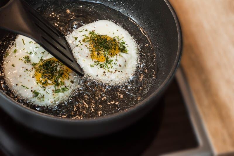 Μαγείρεμα των τηγανισμένων αυγών με τα χορτάρια και το πιπέρι στοκ εικόνα με δικαίωμα ελεύθερης χρήσης