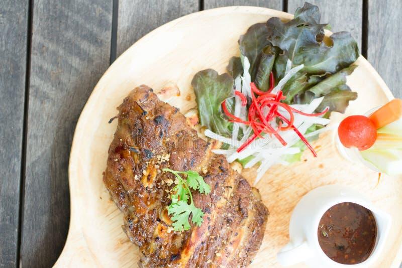 Μαγειρευμένη σχάρα χοιρινού κρέατος πλευρών στο ξύλινο πιάτο στοκ φωτογραφία