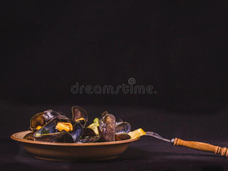 Μαγειρευμένο μύδι στο πιάτο σε ένα μαύρο υπόβαθρο, κινηματογράφηση σε πρώτο πλάνο στοκ εικόνες