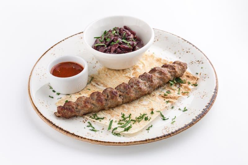 Μαγειρευμένο kofta αρνιών shish kofte kebab με τα φασόλια και το pita που απομονώνονται στο άσπρο υπόβαθρο στοκ φωτογραφία με δικαίωμα ελεύθερης χρήσης