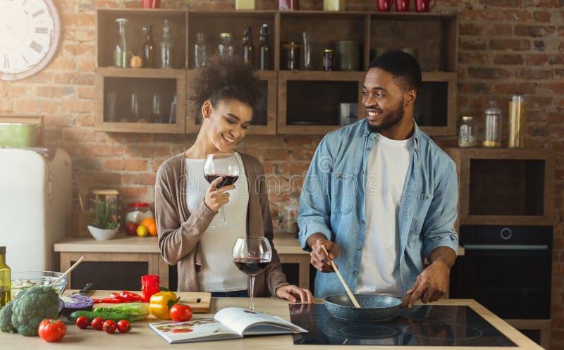 Μαγειρεύοντας γεύμα ζευγών αφροαμερικάνων και κόκκινο κρασί κατανάλωσης στοκ φωτογραφία