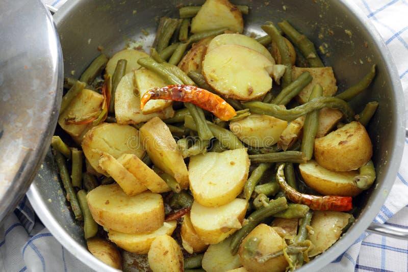 Μαγειρεύοντας κάρρυ πατατών και φασολιών στοκ εικόνα
