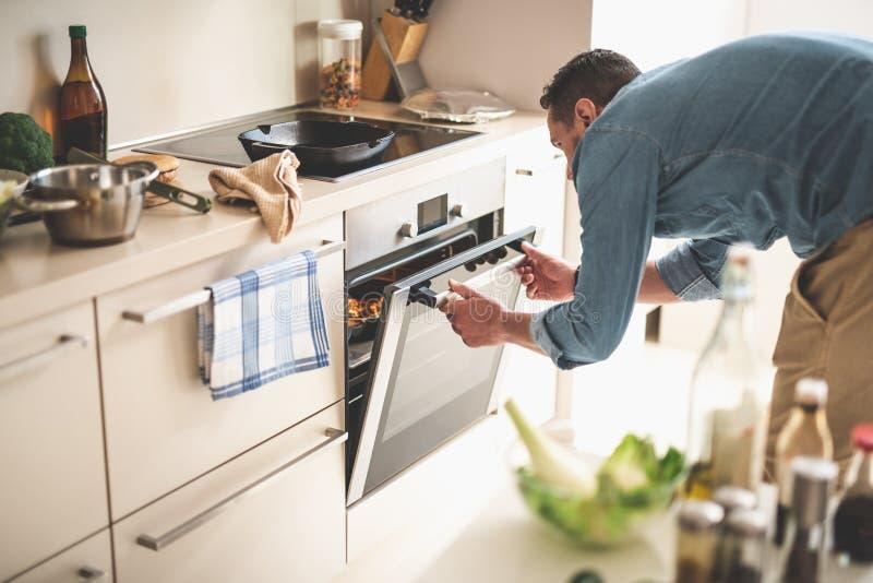 Μαγειρεύοντας κρέας νεαρών άνδρων στο φούρνο στο σπίτι στοκ εικόνα