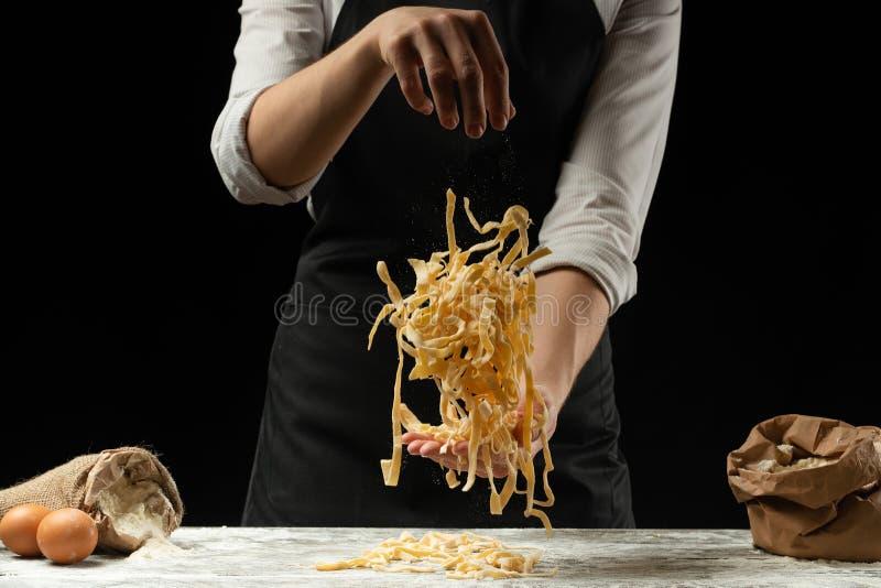 Μαγειρεύοντας μακαρόνια, ιταλικά ζυμαρικά, ζυμαρικά σε ένα μαύρο υπόβαθρο Παγετός στον αέρα με τα μόρια αλευριού Έμβλημα τροφίμων στοκ εικόνες