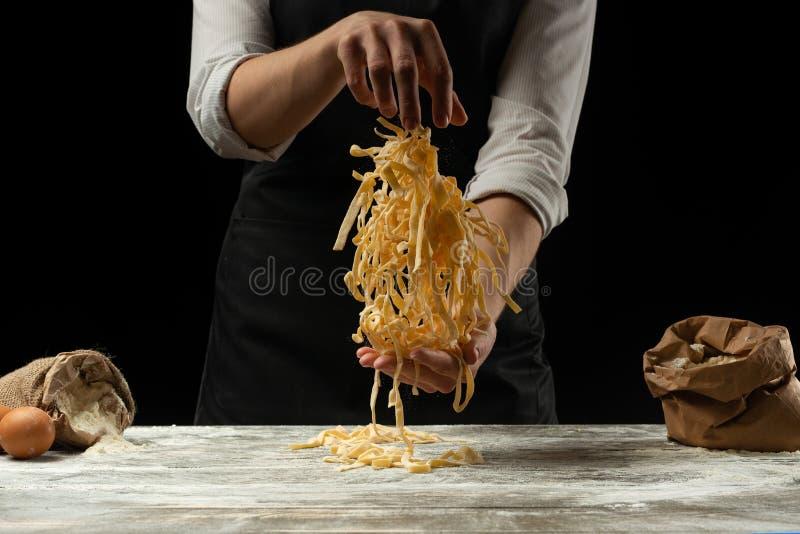 Μαγειρεύοντας μακαρόνια, ιταλικά ζυμαρικά, ζυμαρικά σε ένα μαύρο υπόβαθρο Παγετός στον αέρα με τα μόρια αλευριού Έμβλημα τροφίμων στοκ φωτογραφίες με δικαίωμα ελεύθερης χρήσης