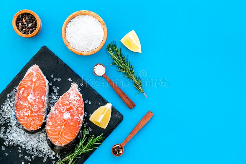 Μαγειρεύοντας μπριζόλα σολομών από τα ακατέργαστα ψάρια στο μαύρο πιάτο με τα καρυκεύματα, το δεντρολίβανο, το λεμόνι και το άλας στοκ εικόνα με δικαίωμα ελεύθερης χρήσης