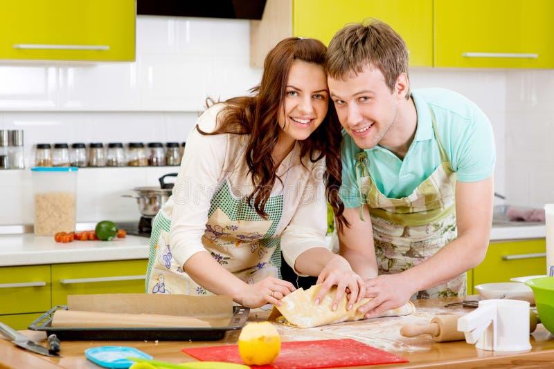 Μαγειρεύοντας πίτα μήλων παντρεμένου ζευγαριού στην κουζίνα στο σπίτι στοκ εικόνες