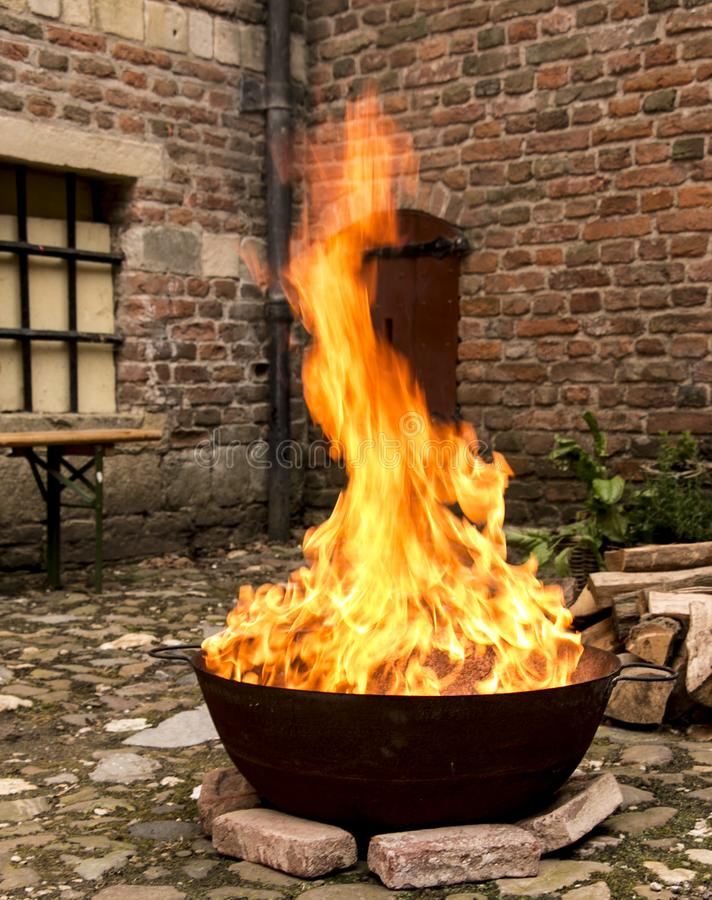 Μαγειρεύοντας πυρκαγιά σε ένα κάστρο σε μια κατσαρόλα στοκ φωτογραφία