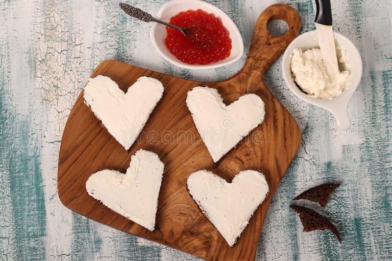 Μαγειρεύοντας σάντουιτς με το κόκκινο τυρί χαβιαριών και κρέμας με μορφή μιας καρδιάς για την ημέρα του βαλεντίνου στοκ φωτογραφία με δικαίωμα ελεύθερης χρήσης