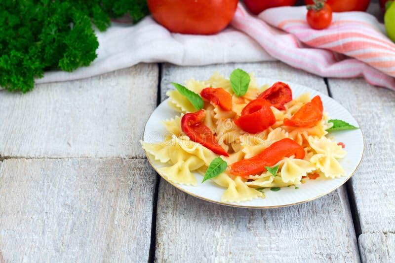 μαγειρεύοντας συστατικά ιταλικά τροφίμων Fusilli ζυμαρικών με τη σάλτσα, τα πιπέρια και το βασιλικό ντοματών στο ξύλινο υπόβαθρο στοκ φωτογραφίες
