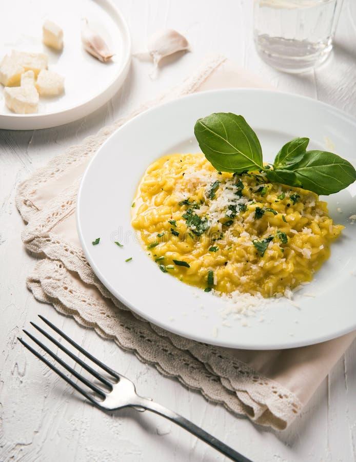 μαγειρεύοντας συστατικά ιταλικά τροφίμων Risotto με το τυρί σε ένα άσπρο πιάτο σε ένα άσπρο υπόβαθρο στοκ εικόνα