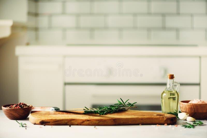 Μαγειρεύοντας συστατικά τροφίμων στο άσπρο εσωτερικό υπόβαθρο σχεδίου κουζινών με τον αγροτικό ξύλινο τεμαχίζοντας πίνακα στο κέν στοκ φωτογραφία