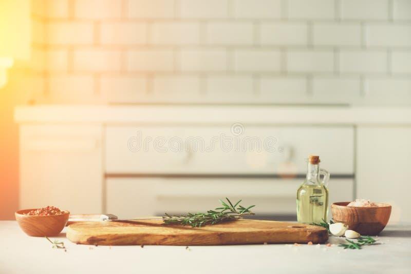 Μαγειρεύοντας συστατικά τροφίμων στο άσπρο εσωτερικό υπόβαθρο σχεδίου κουζινών με τον αγροτικό ξύλινο τεμαχίζοντας πίνακα στο κέν στοκ εικόνες