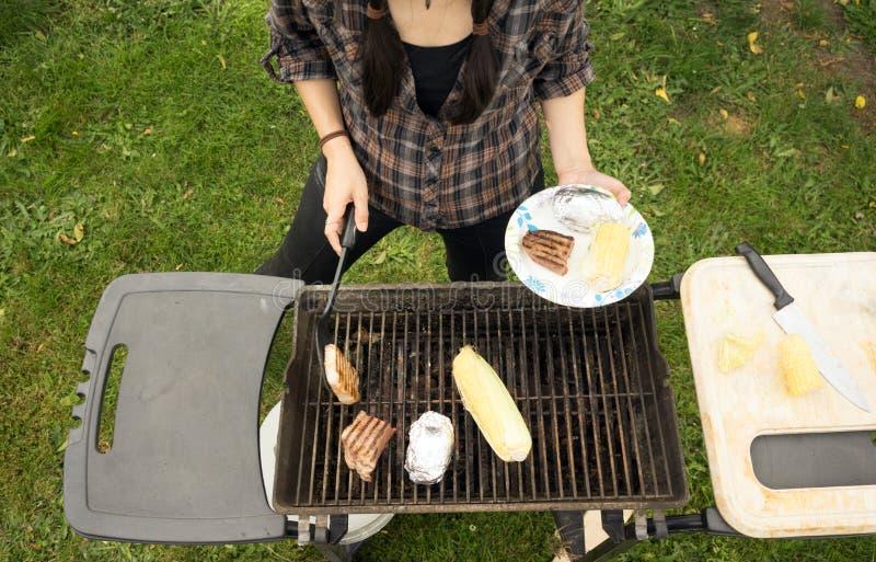 Μαγειρεύοντας σχάρα τροφίμων κατωφλιών σχαρών μπριζολών κορμών γυναικών στοκ φωτογραφία με δικαίωμα ελεύθερης χρήσης