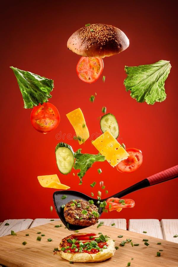 Μαγειρεύοντας χάμπουργκερ με τις πετώντας ντομάτες, το τυρί και τα χορτάρια στοκ εικόνες με δικαίωμα ελεύθερης χρήσης