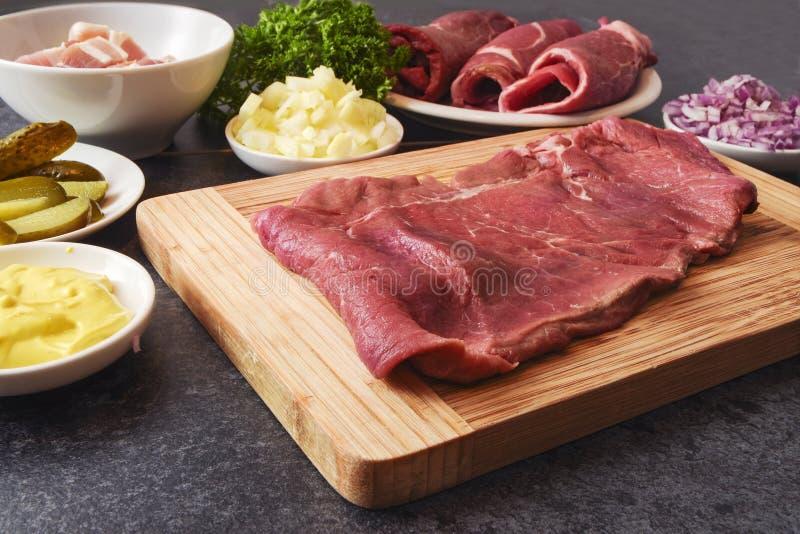 Μαγειρεύοντας roulades βόειου κρέατος με τα συστατικά ως μουστάρδα, κρεμμύδια, π στοκ εικόνες