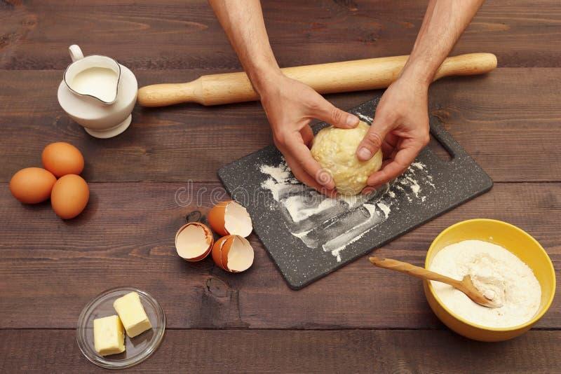 Μαγειρικά χέρια που γονατίζουν ζύμη για ψήσιμο στο σανίδα πάνω σε ξύλινο τραπέζι στοκ εικόνα με δικαίωμα ελεύθερης χρήσης