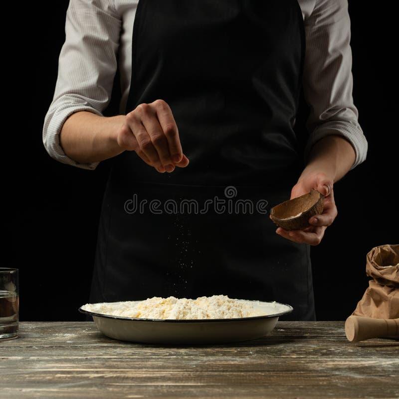 μαγειρική Ο μάγειρας μαγειρεύει τη ζύμη για τα ζυμαρικά, πίτσα, ψωμί Ψεκάζει με το άλας Εύγευστα τρόφιμα, συνταγές, μαγείρεμα, γα στοκ φωτογραφίες