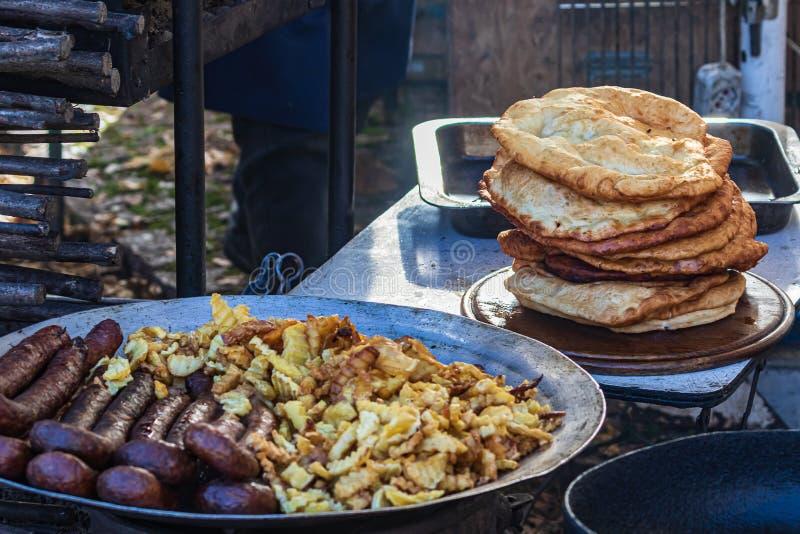 Μαγειρικός μπουφές με υγιεινό φαγητό σε τακτά διαστήματα - νόστιμα λουκάνικα και πατάτες σε ένα δρόμο στοκ εικόνα