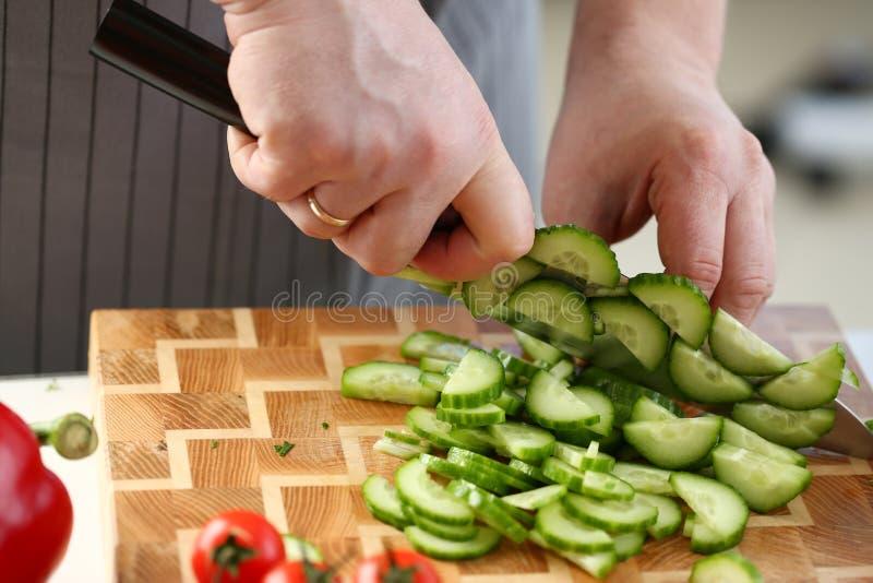 Μαγειρικό αρσενικό που τεμαχίζει το πράσινο να κάνει δίαιτα αγγούρι στοκ εικόνες