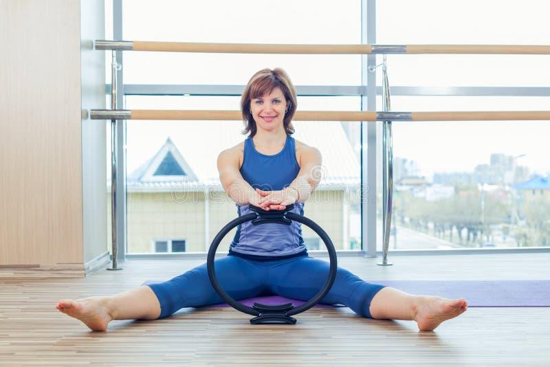 Μαγική άσκηση χεριών δαχτυλιδιών γυναικών Pilates workout στη γυμναστική εσωτερική στοκ εικόνες
