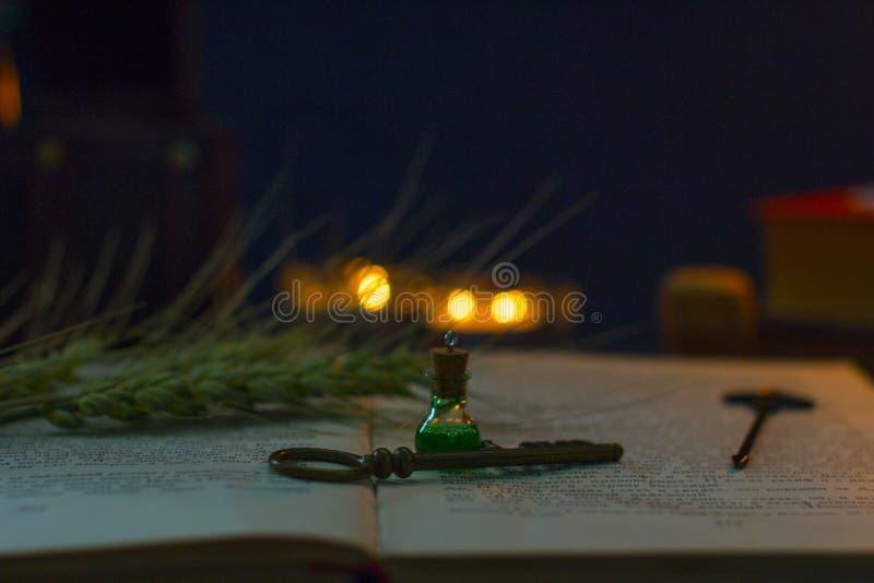 Μαγική φίλτρο, αρχαία βιβλία και κεριά στο σκοτεινό υπόβαθρο στοκ εικόνες