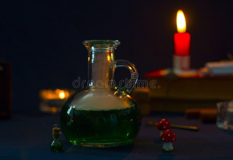 Μαγική φίλτρο, αρχαία βιβλία και κεριά στο σκοτεινό υπόβαθρο στοκ εικόνα